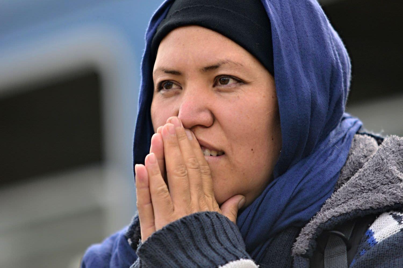 Bild zeigt: Ein junge Migrantin mit Kopftuch und vor dem Mund gefalteten Händen