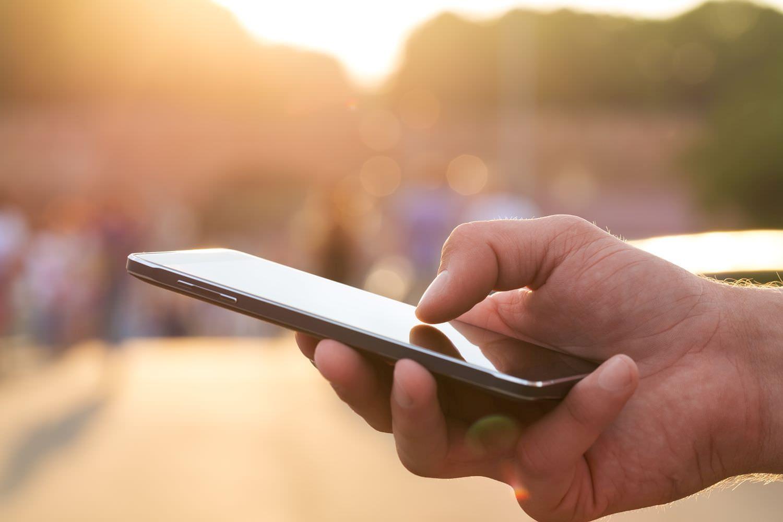 Bild zeigt: Großaufnahme einer Hand, die ein Smartphone hält und bedient