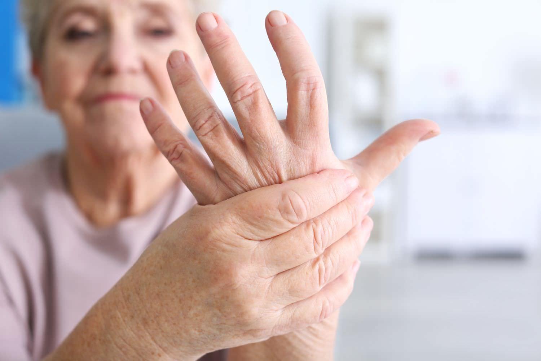 Bild zeigt: Ältere Frau hält mit einer Hand die andere schmerzende Hand