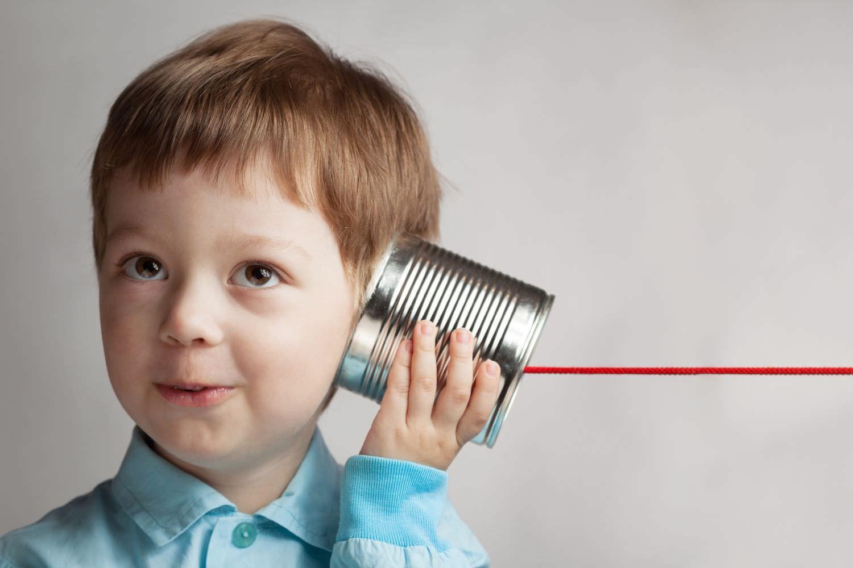 Bild zeigt: Einen kleinen glücklichen Jungen, der mit einer Blechdose Telefon spielt