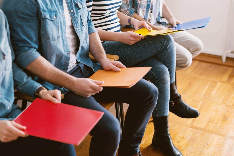 Bild zeigt: Zwei Männer und zwei Frauen mit Mappen in den Händen warten auf Stühlen auf ihr Bewerbungsgespräch