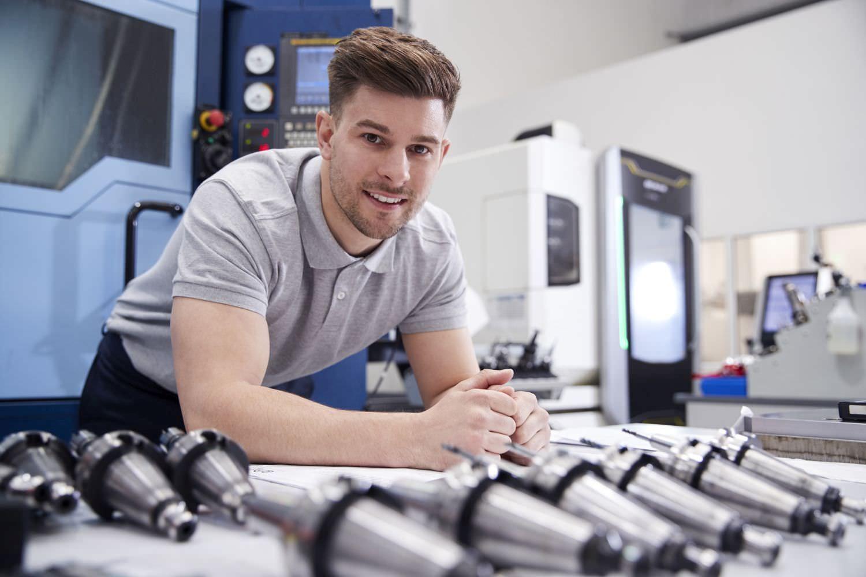 Bild zeigt: Portrait eines jungen Facharbeiters vor der CNC-Werkbank
