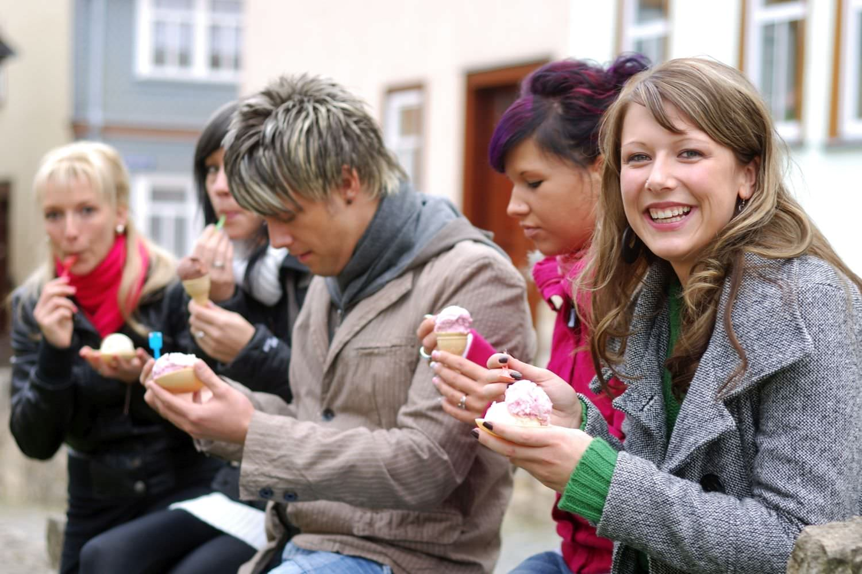 Bild zeigt: Gruppe junger Erwachsener beim Eisessen in der Stadt