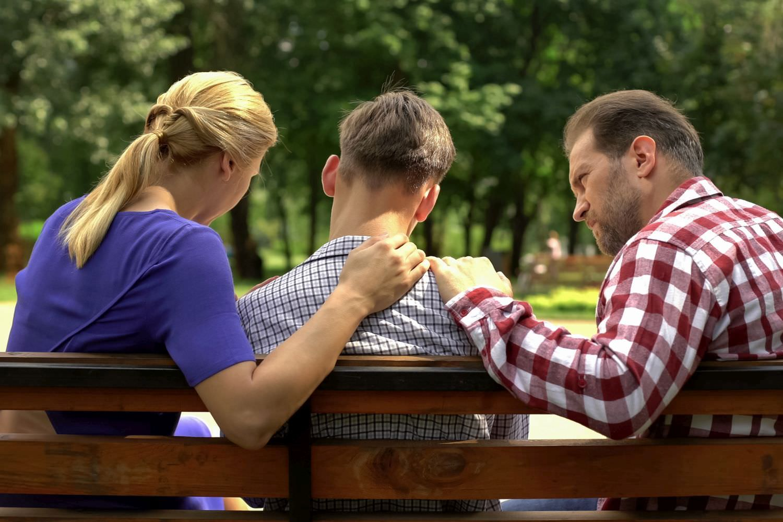 Bild zeigt: Eltern mit Jugendlichem von hinten auf einer Parkbank