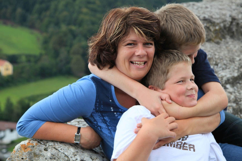 Bild zeigt: Mutter wird von ihren zwei Söhnen umarmt