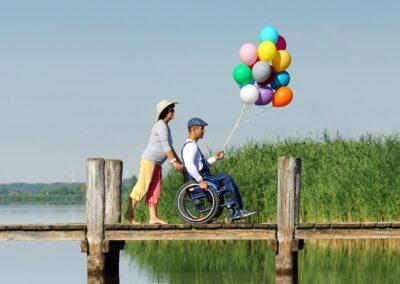 Bild zeigt: Ein Mann mit Behinderung in einem Rollstuhl hält ein Bündel bunter Luftballons in der Hand