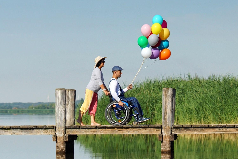 Behinderter Mann im Rollstuhl am See hält ein Bündel bunter Helium-Luftballons