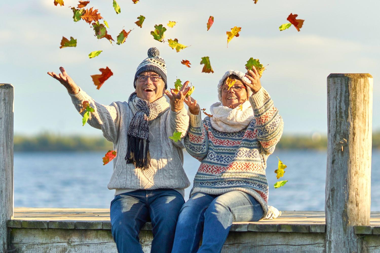 Bild zeigt: Älteres Paar sitzt im Herbst auf einem Bootsanleger