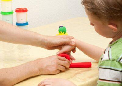 Bild zeigt: Ergotherapeut erklärt einem Jungen eine Übung für die Hand mit roter Knete