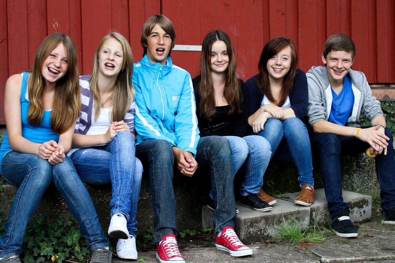 Bild zeigt: Sechs fröhliche Teenies vor einer dunkelroten Bretterwand