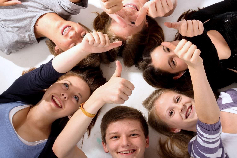Bild zeigt: Gruppe Jugendlicher liegt im Kreis auf dem Boden und hebt den Daumen hoch