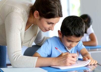 Bild zeigt: Lehrerin hilft einem Jungen mit Migrationshintergrund beim Schreiben im Heft