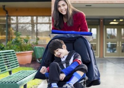 Bild zeigt: Ein Junge im Rollstuhl mit seiner Integrationshelferin vor dem Schuleingang