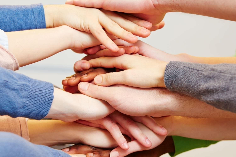 Bild zeigt: Die Hände vieler junger Menschen sind zu einem Turm gestapelt