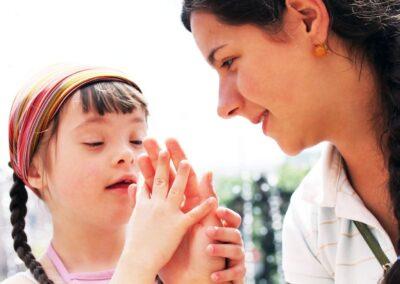 Bild zeigt: Mädchen mit Behinderung greift in die offene Hand der Mutter