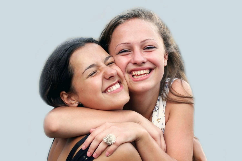 Bild zeigt: Zwei junge Frauen umarmen sich glücklich