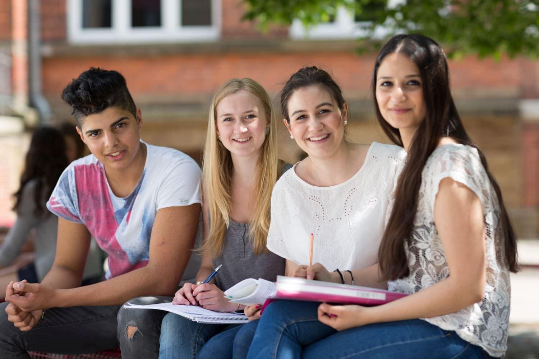 Bild zeigt: Gemischte fröhliche Gruppe von Teenagern lernt auf dem Schulhof