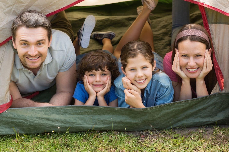 Bild zeigt: Familie mit zwei Kindern im Eingang eines Hauszeltes
