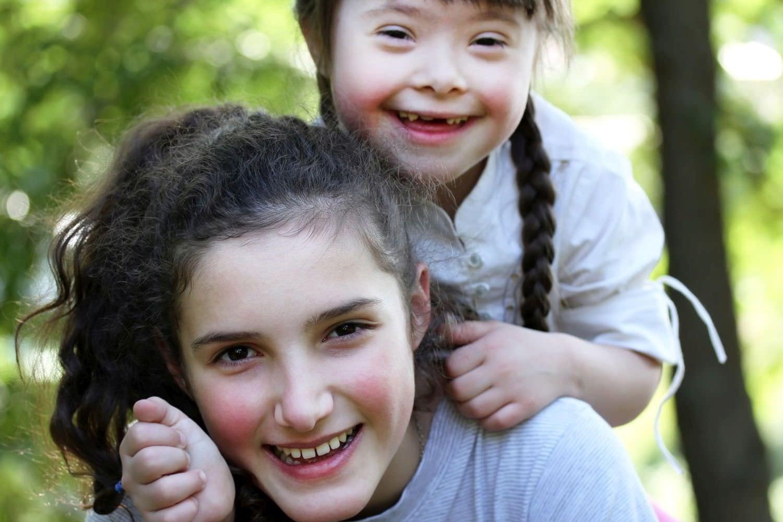 Bild zeigt: Ein Mädchen mit Down-Syndrom wird von ihrer älteren Schwester auf dem Rücken getragen