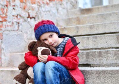 Bild zeigt: Kleiner trauriger Junge sitzt auf einer Steintreppe und hält sein Stofftier