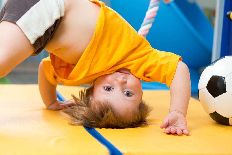 Bild zeigt: Ein kleiner Junge verbiegt sich mit dem Kopf nach unten auf einer Turnmatte
