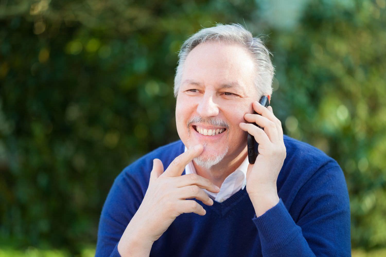 Bild zeigt: Mann mit grau-weißem Bart telefoniert mit dem Handy