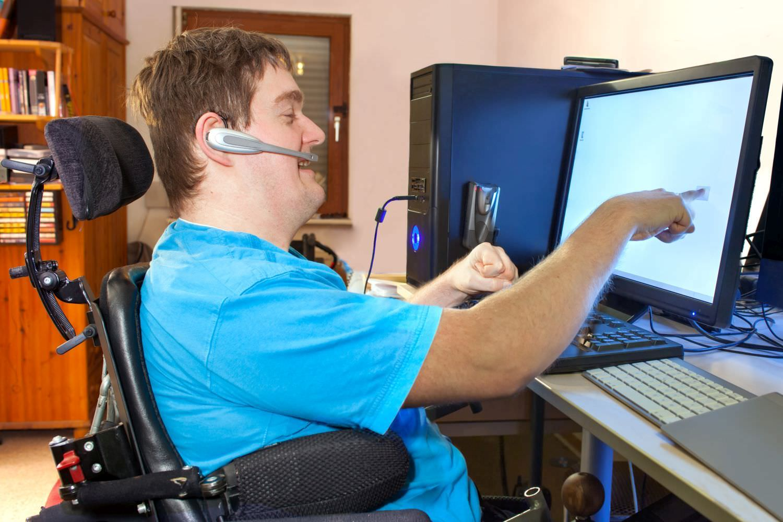 Bild zeigt: Ein Mann mit Behinderung im Rollstuhl arbeitet mit Headset an einem Computer