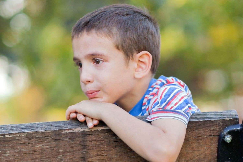 Bild zeigt: Portrait eines traurigen kleinen Jungen auf einer Parkbank