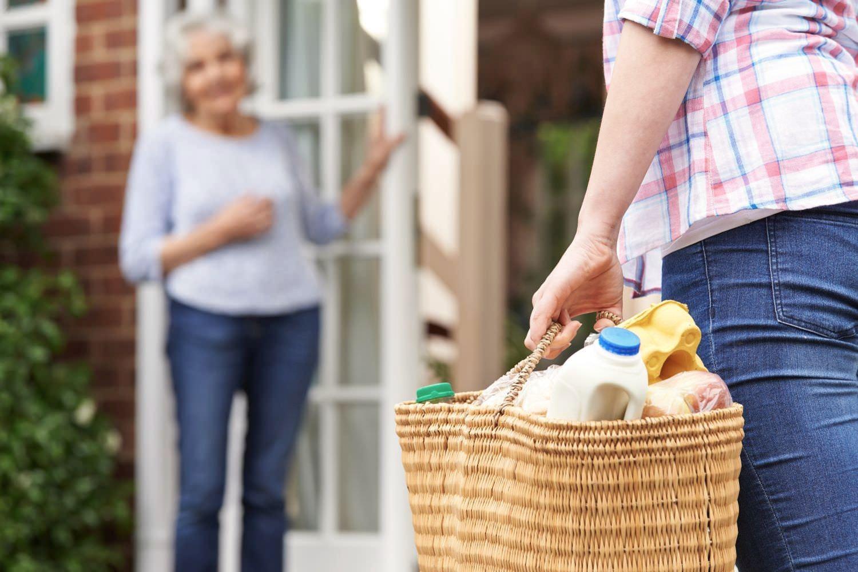 Bild zeigt: Eine junge Frau bringt den Einkauf für eine Seniorin