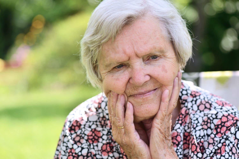 Bild zeigt: Ältere Frau stützt nachdenklich den Kopf auf ihre Hände