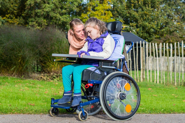 Bild zeigt: Eine junge Frau beugt sich zu einer jungen behinderten Frau im Rollstuhl