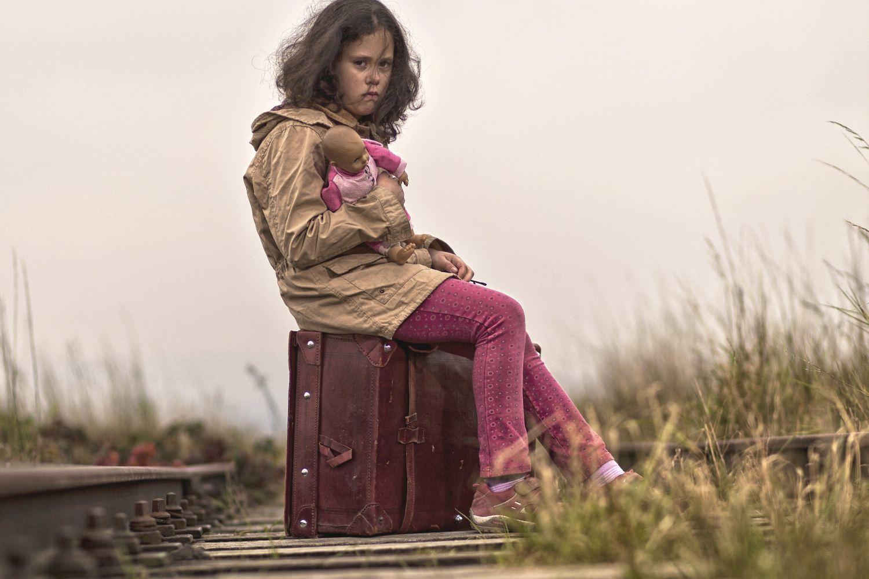 Bild zeigt: Flüchtlingsmädchen sitzt auf einem Koffer auf Gleisen