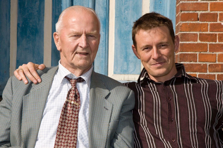 Bild zeigt: Älterer Mann und sein Betreuer nebeneinander in der Sonne