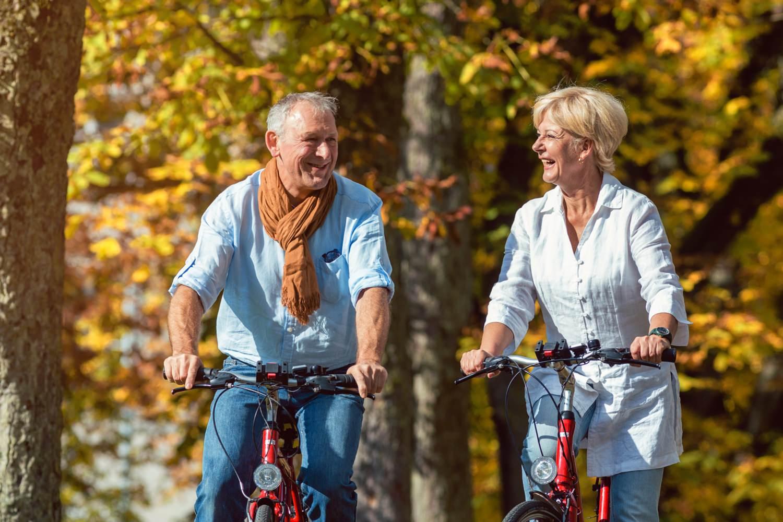 Bild zeigt: Ein Mann und eine Frau im Alter 50+ mit ihren Fahrrädern im Herbst