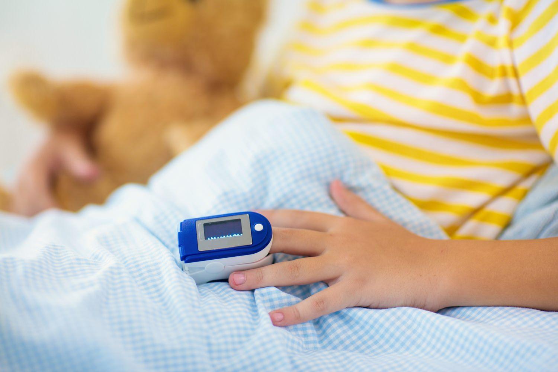 Bild zeigt: Kranker Junge im Bett mit Messgerät am Finger