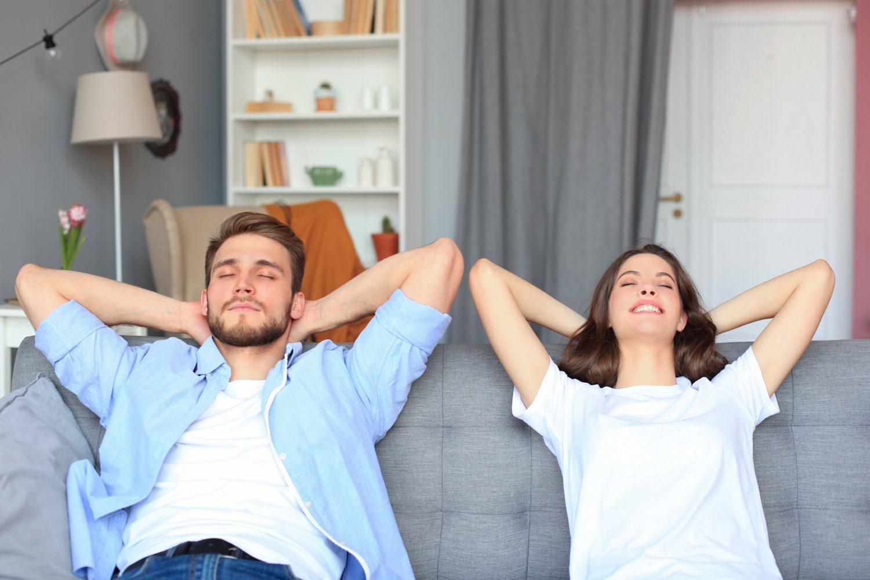 Bild zeigt: Junger Mann und junge Frau entspannen auf einem Sofa
