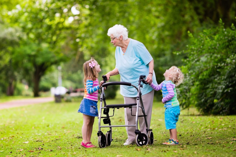 Bild zeigt: Zwei Enkelkinder mit ihrer gehbehinderten Großmutter im Park
