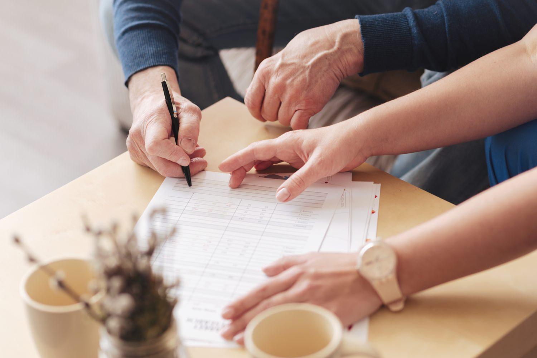 Bild zeigt: Ein Senior beim Ausfüllen eines Formulars