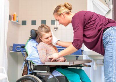 Bild zeigt: Ein Mädchen im Rollstuhl mit schwerer Behinderung bekommt von einer jungen Frau das Gesicht gewaschen