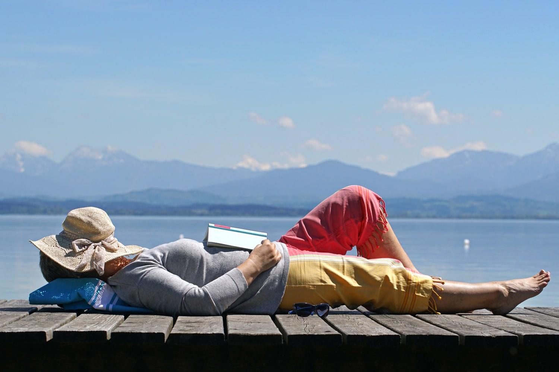 Bild zeigt: Eine ältere Frau mit einem Buch auf einem Bootssteg in der Sonne