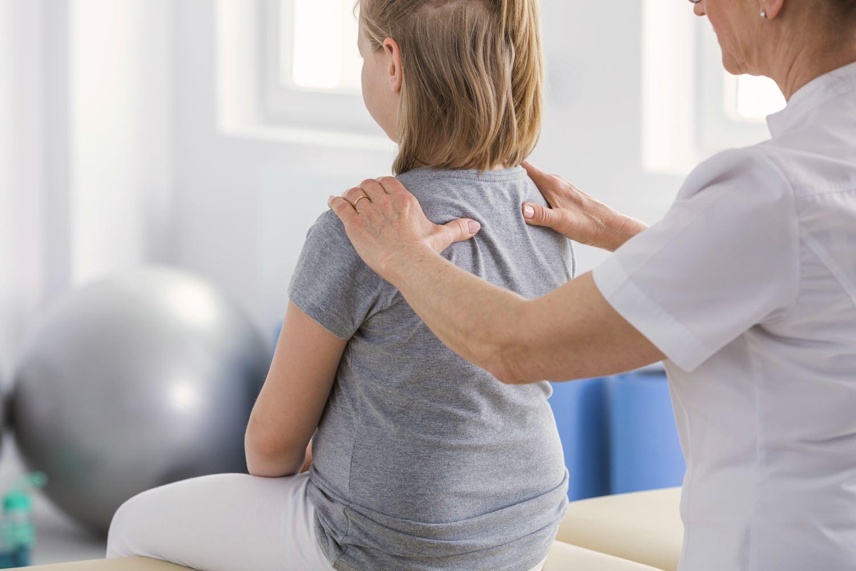 Bild zeigt: Physiotherapeutin behandelt in der Praxis ein Mädchen am Rücken