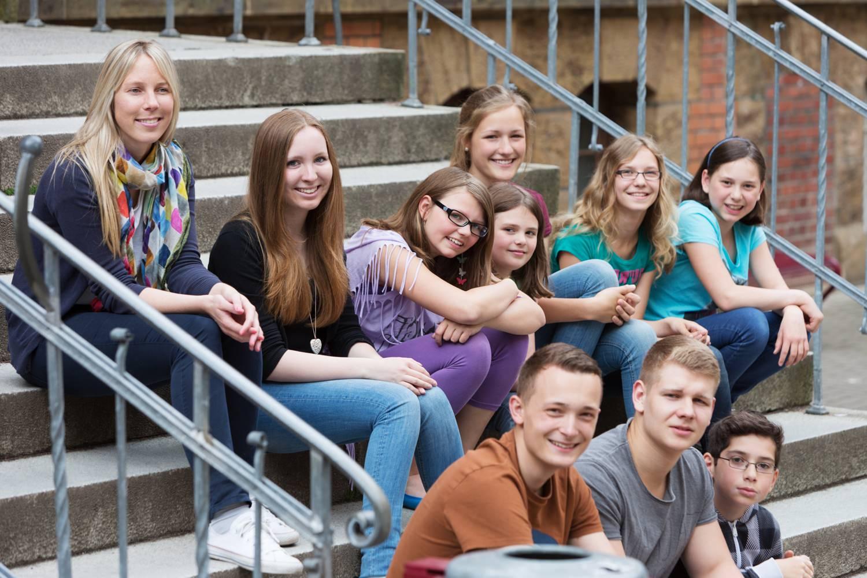 Bild zeigt: Eine Gruppe von Teenies sitzt zusammen auf einer Außentreppe