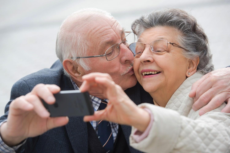 Bild zeigt: Seniorenpaar fotografiert sich mit dem HandyZwei Senioren machen ein Foto, während der Mann die Frau auf die Wange küsst