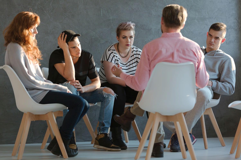 Bild zeigt: Junge Erwachsene in einer Gesprächsrunde mit einem Therapeuten