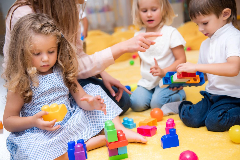Bild zeigt: Kleinkinder und Betreuerin spielen mit Bauklötzen