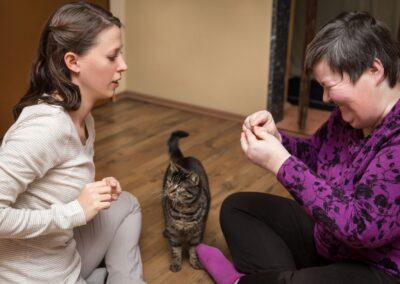 Bild zeigt: Geistig behinderte Frau mit Betreuuerin und Katze