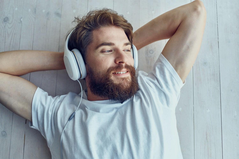 Bild zeigt: Junger Mann liegt auf dem Boden und hört Musik