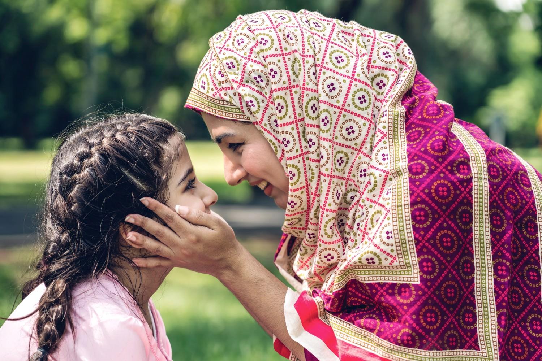 Bild zeigt: Glückliche muslimische Mutter mit ihrer Tochter in einem Park