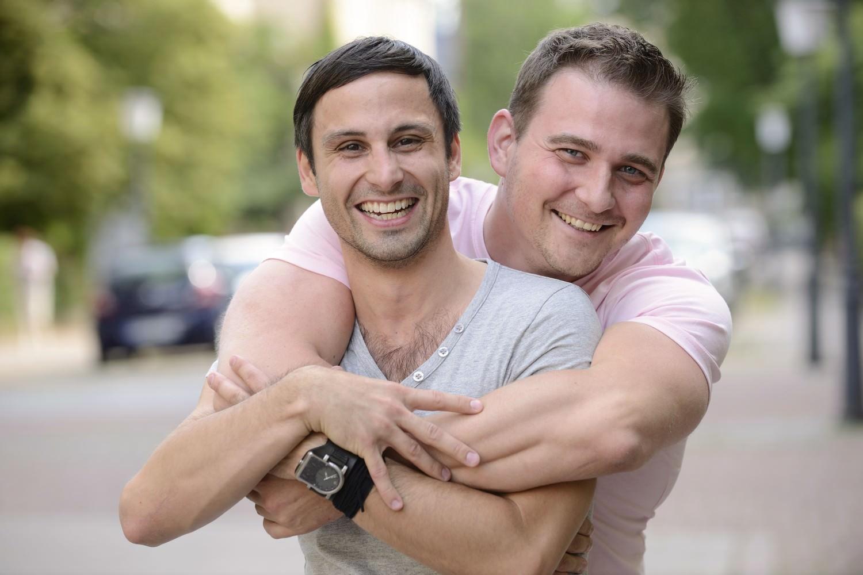 Bild zeigt: Zwei homosexuelle Männer umarmen sich lachend