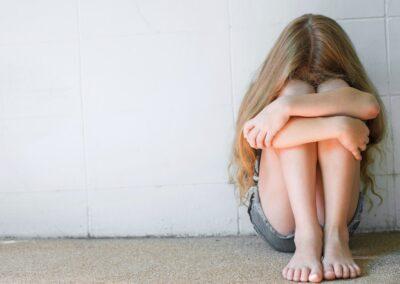 Bild zeigt: Mädchen hockt zusammengekauert vor einer Wand